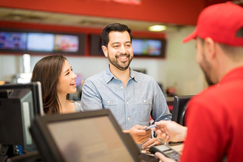 Mężczyzna kupienia filmu bilety dla jego dziewczyny zdjęcie royalty free