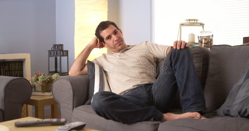 Mężczyzna lounging na kanapie obrazy royalty free
