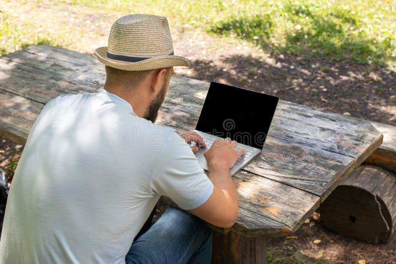 Mężczyzna lub facet pracuje na komputerze z pustym ekranem dla kopii przestrzeni, siedzi na ławce w lecie outdoors fotografia stock