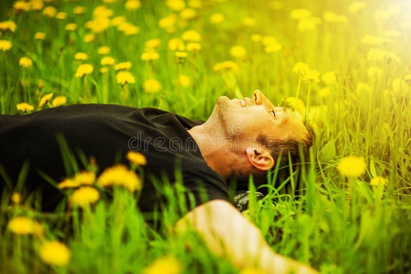 Mężczyzna lying on the beach na trawie przy słonecznym dniem obrazy royalty free