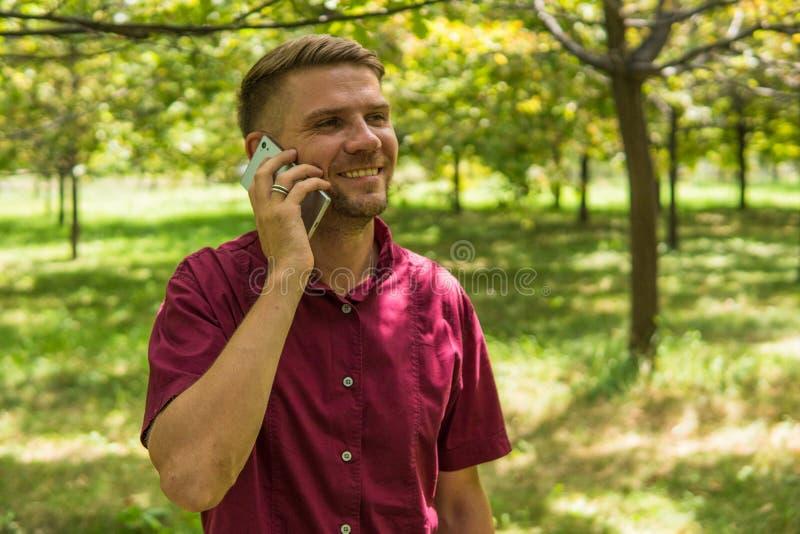 Mężczyzna mówienie na telefonie komórkowym w parku Młody atrakcyjny mężczyzna w zdjęcie royalty free