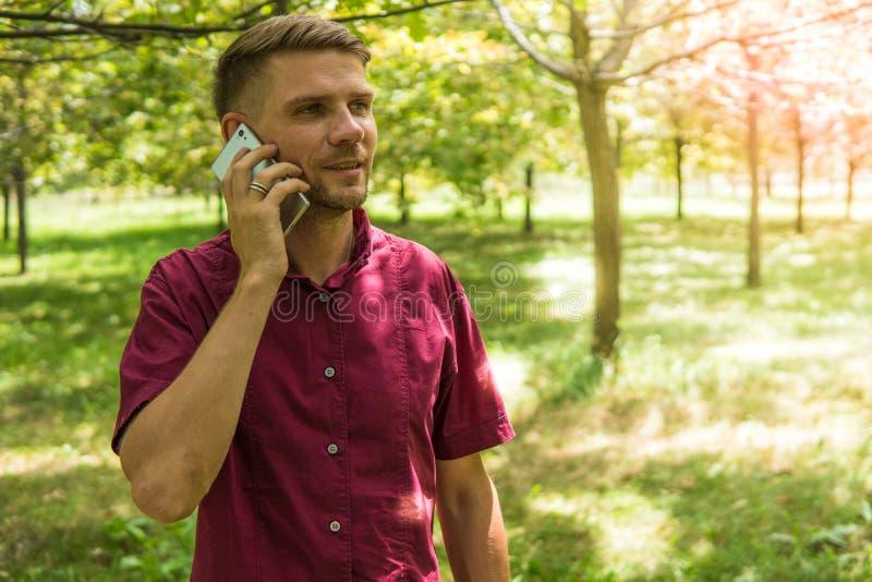 Mężczyzna mówienie na telefonie komórkowym w parku Młody atrakcyjny mężczyzna w obrazy stock