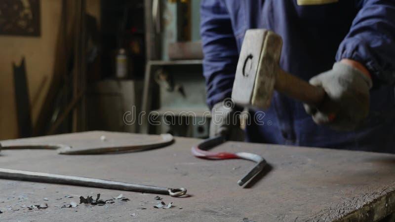 Mężczyzna młotkuje żelaznego haczyka z młotem obrazy royalty free
