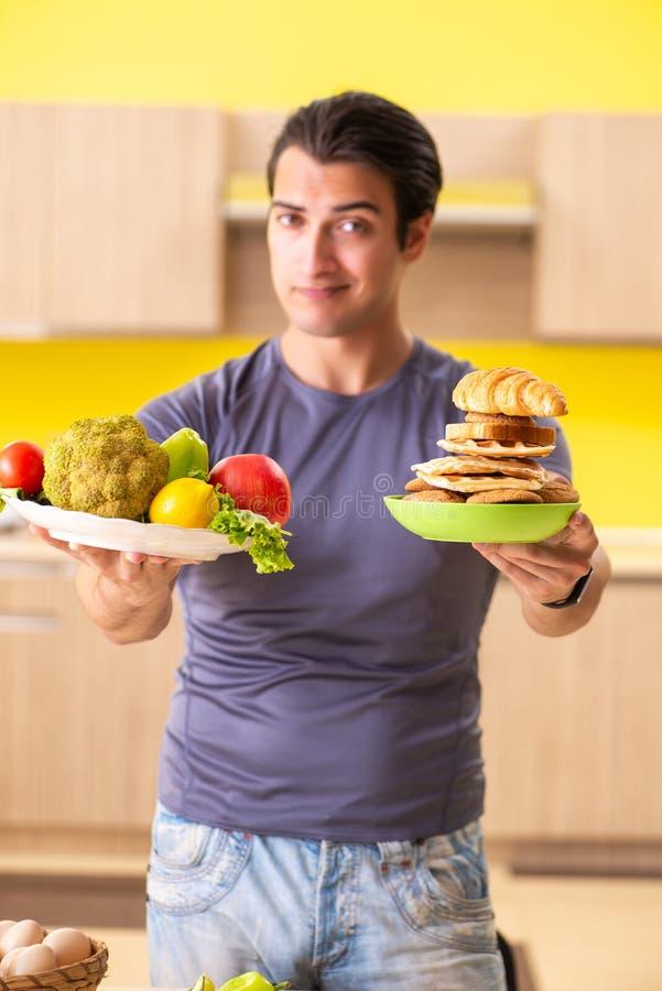 Mężczyzna ma ciężkiego wybór między zdrowym i niezdrowym jedzeniem obraz royalty free