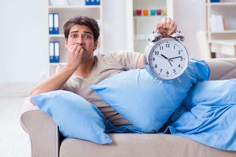 Mężczyzna ma kłopot budzi się up z budzikiem zdjęcia royalty free