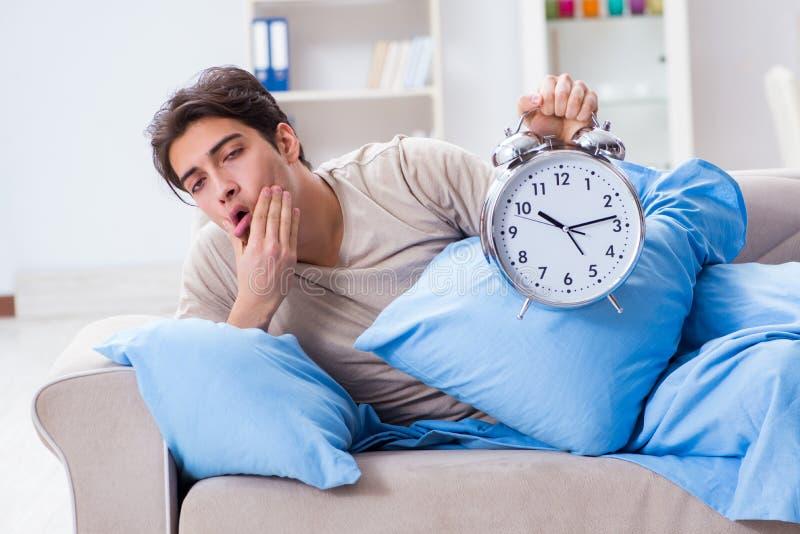 Mężczyzna ma kłopot budzi się up z budzikiem obraz stock