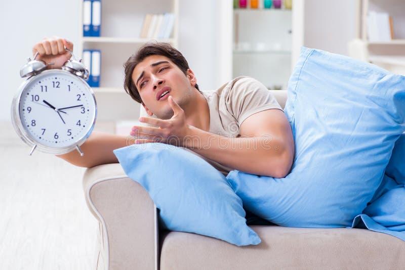 Mężczyzna ma kłopot budzi się up z budzikiem obrazy stock