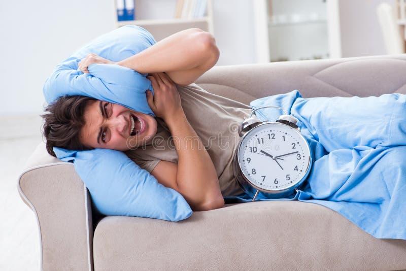 Mężczyzna ma kłopot budzi się up z budzikiem zdjęcie stock