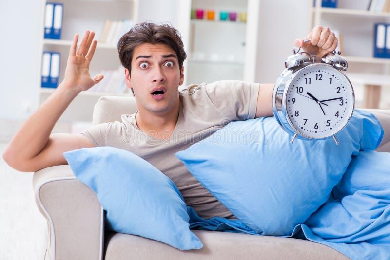 Mężczyzna ma kłopot budzi się up z budzikiem fotografia stock