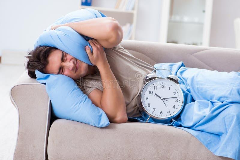 Mężczyzna ma kłopot budzi się up z budzikiem zdjęcia stock