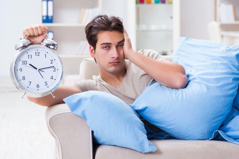 Mężczyzna ma kłopot budzi się up z budzikiem fotografia royalty free