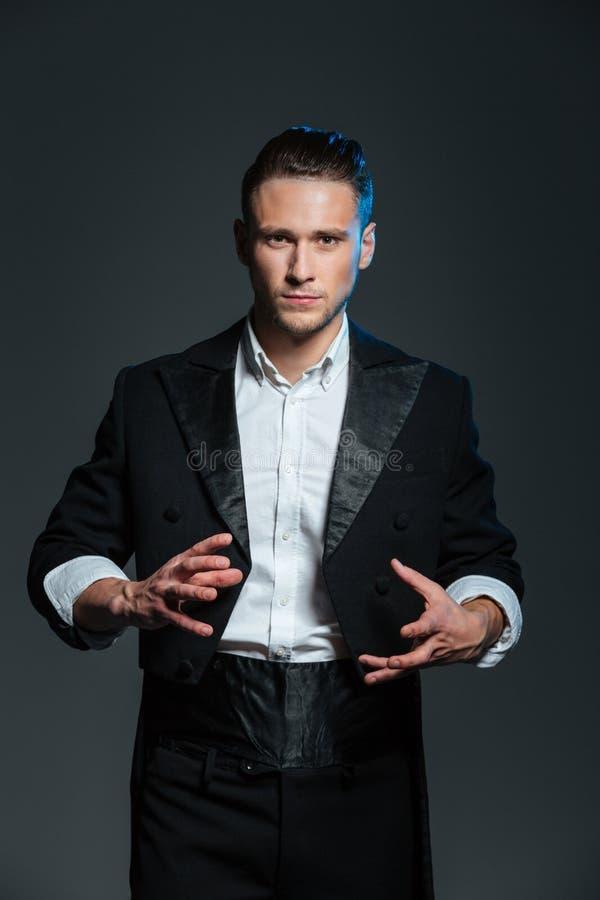 Mężczyzna magik czaruje sztuczki w tylnym ogonu żakiecie zdjęcia royalty free