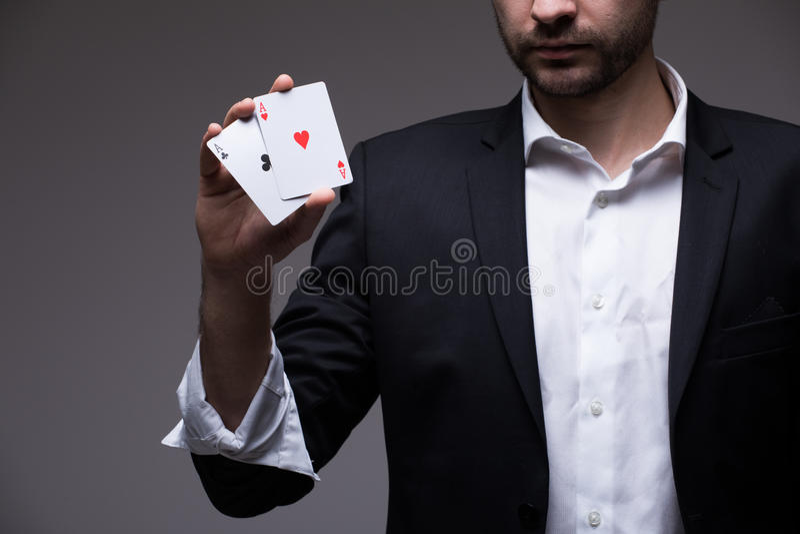 Mężczyzna magik z dwa karta do gry w jego oddawał popielatego tło fotografia stock