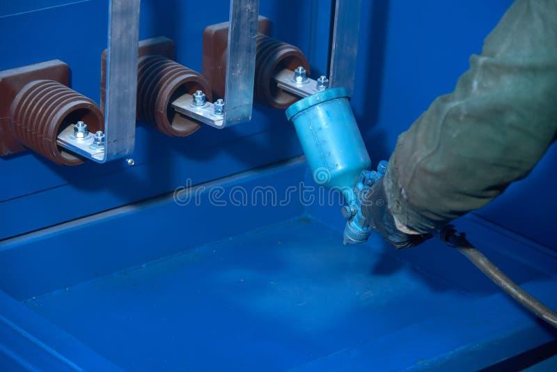 Mężczyzna maluje z błękitną farbą z metali produktów kiści pistoletem fotografia stock