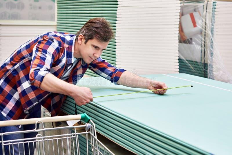 Mężczyzna miary z ruletowym drywall ciąć na arkusze w sklepu budynku szturmanie zdjęcie stock