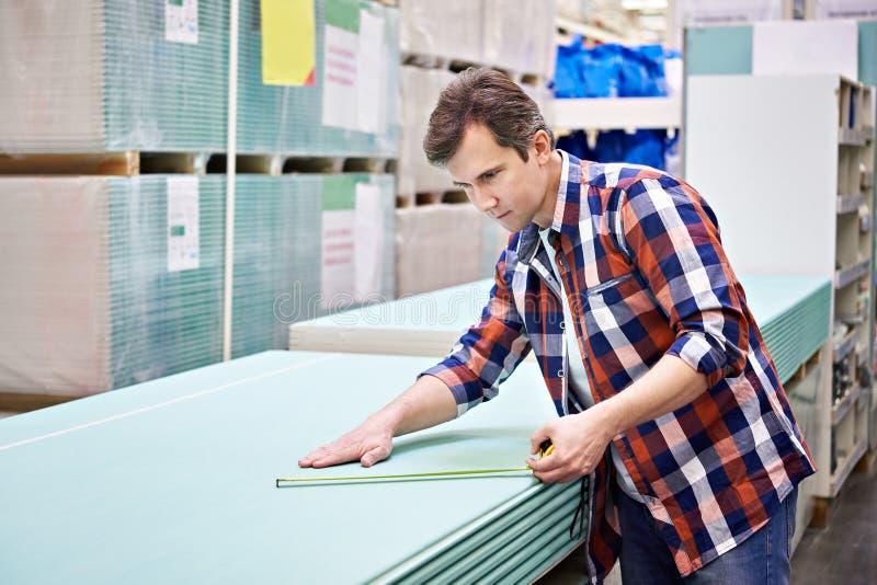 Mężczyzna miary z ruletowym drywall ciąć na arkusze w sklepu budynku szturmanie fotografia royalty free