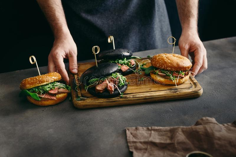 Mężczyzna mienia deski różni hamburgery piec na grillu wzmacniają mięso obraz royalty free