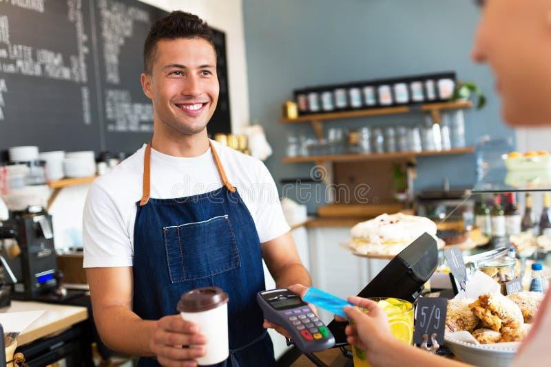 Mężczyzna mienia kredyta czytnik kart przy kawiarnią obrazy stock