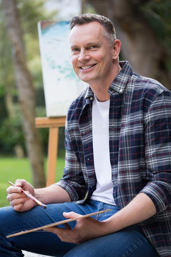 Mężczyzna mienia muśnięcie w ogródzie i paleta zdjęcie royalty free