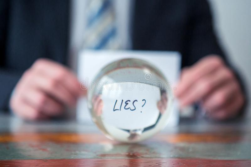 Mężczyzna mienia papier z słowem Kłama przed szklaną piłką zdjęcia stock