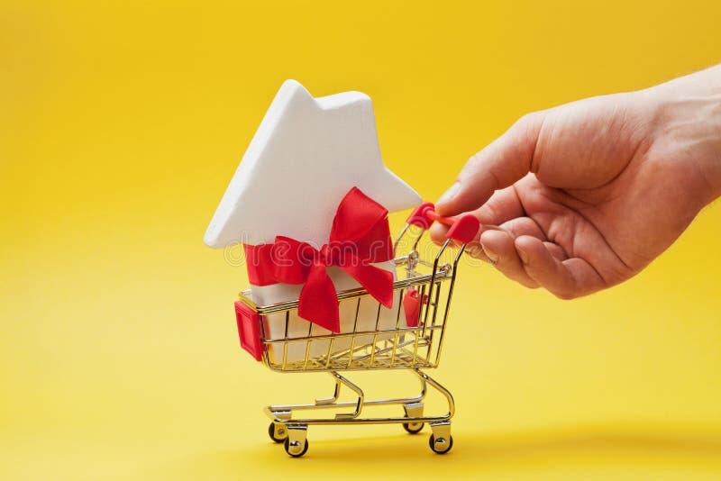 Mężczyzna mienia ręki wózek na zakupy z domem dekorował faborek na żółtym tle Kupować dom, prezent lub sprzedaż nieruchomość nowy fotografia stock