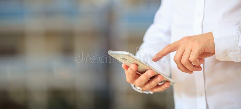 Mężczyzna mienia telefon Młody leworęczny biznesmen w biznesowej odzieży używać wiszącą ozdobę, zbliżenie widok na smartphone, sz fotografia stock