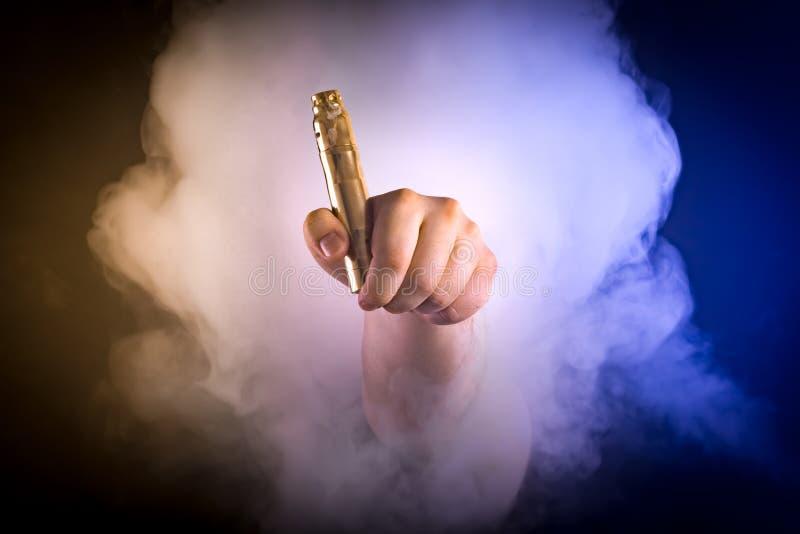 Mężczyzna mienia vaping przyrząd w colour dymu obraz royalty free