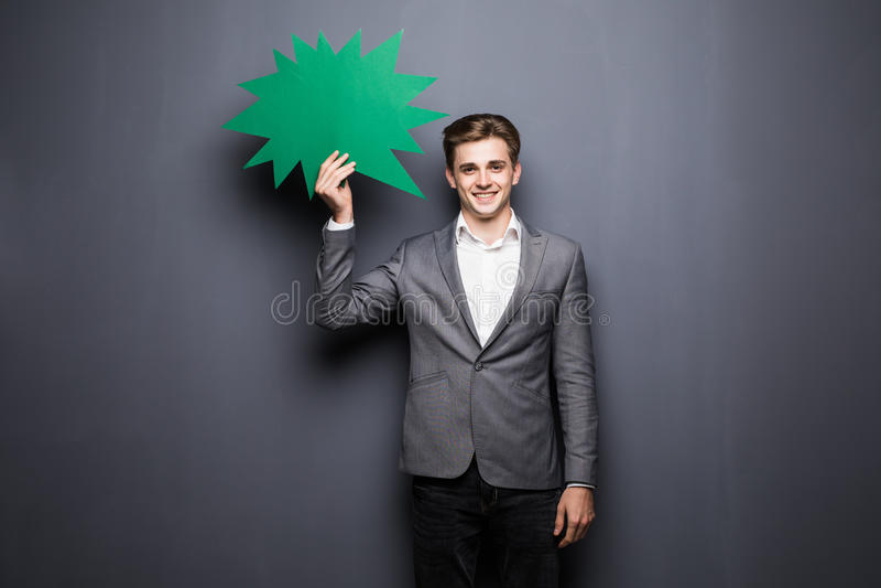 Mężczyzna mienia zieleni mowy pusty bąbel z przestrzenią dla teksta na popielatym tle fotografia royalty free