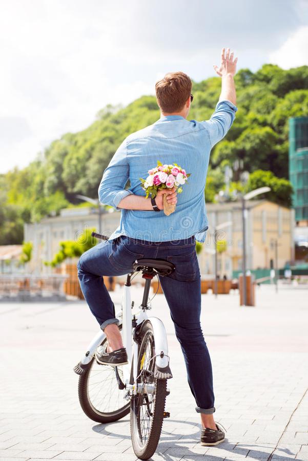 Mężczyzna mienie kwitnie za jego z powrotem zdjęcie royalty free