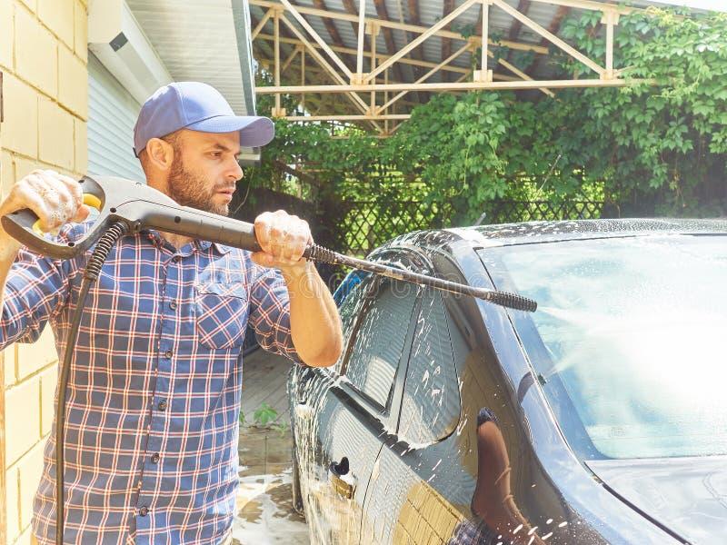 Mężczyzna myje jego czarnego samochodowego pobliskiego dom obraz stock