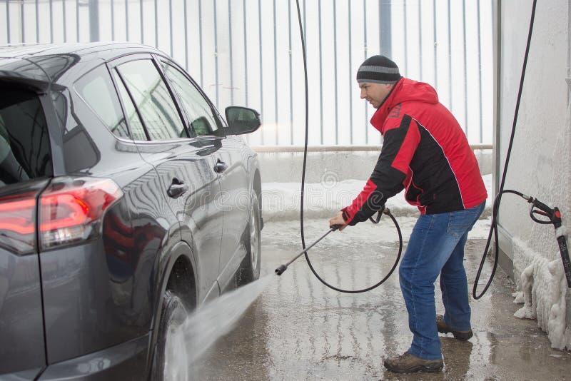 Mężczyzna myje jego samochód w samoobsługi staci z wysokość naciska niszczycielem zdjęcia royalty free