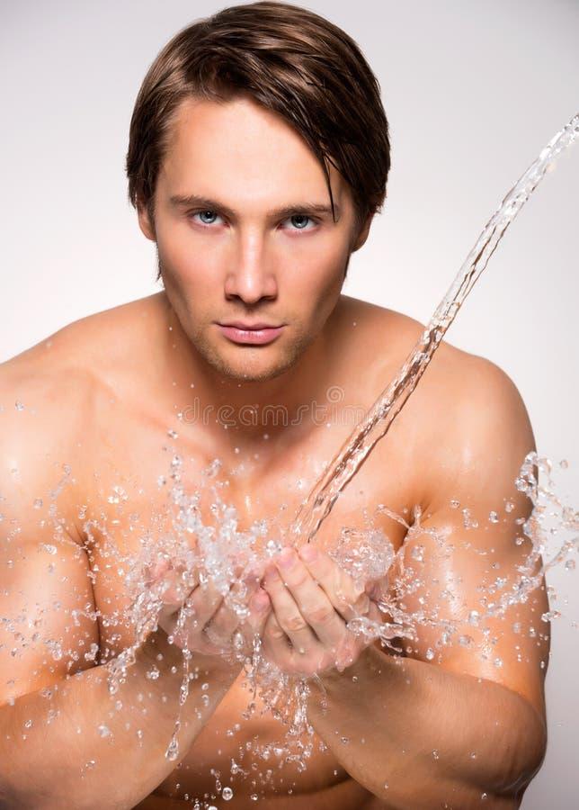 Mężczyzna myje jego twarz z czystą wodą obrazy stock