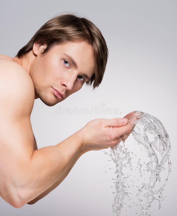 Mężczyzna myje jego twarz z wodą zdjęcie stock