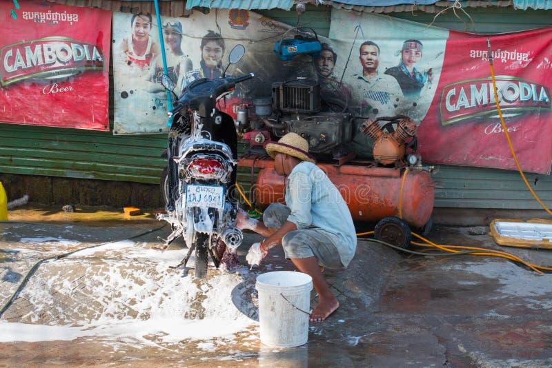 Mężczyzna myje motocykl w Phnom Penh, Kambodża fotografia royalty free