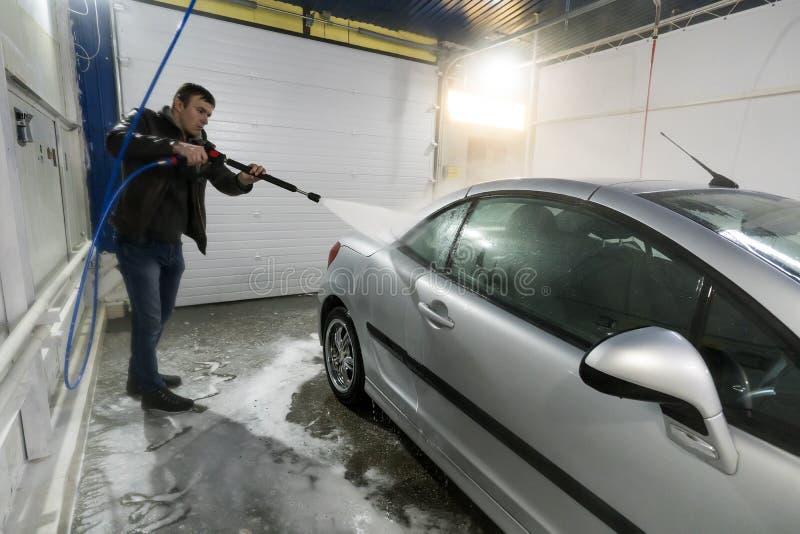Mężczyzna myje samochód w pudełkowatej contactless samochodowego obmycia samoobsłudze z wodnym pistoletem w ręcznym samoobsługowy zdjęcie royalty free