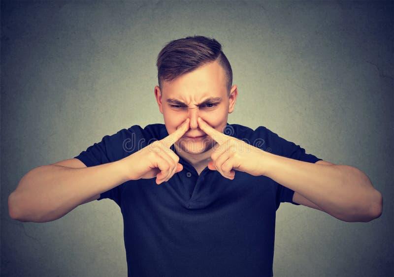 Mężczyzna nękań nos z palców spojrzeniami z obmierzłością coś śmierdzi zdjęcie stock