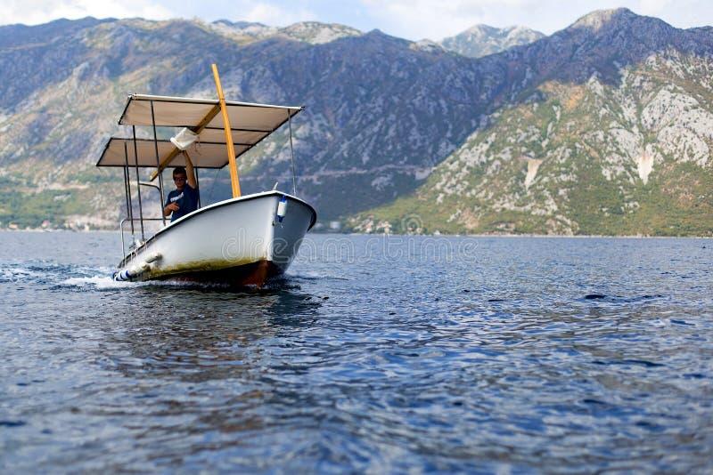 Mężczyzna na łodzi żegluje z turystami, artykuł wstępny obraz royalty free