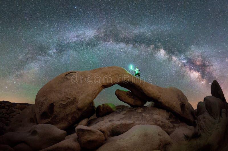 Mężczyzna na łuk skale pod Milky sposobu galaktyką zdjęcie royalty free