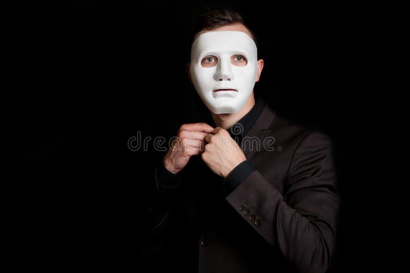 Mężczyzna na czarnym tle w białej masce Zapina guzika na jego koszula obraz royalty free