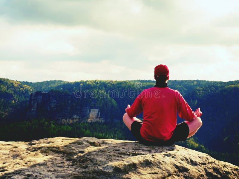 Mężczyzna na górze góry w joga pozie Ćwiczy joga na krawędzi z breathtaking widokiem zdjęcia stock