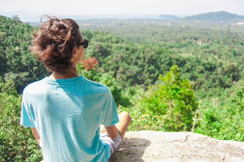 Mężczyzna na górze halnego obsiadania na rockowego dopatrywania malowniczym widoku obraz royalty free