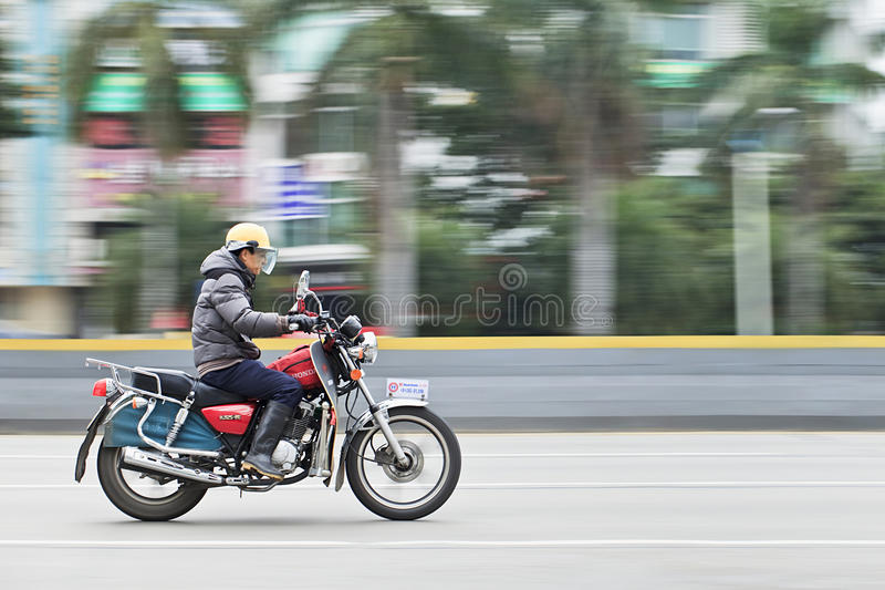 Mężczyzna na Honda motocyklu na drodze, Guangzhou, Chiny fotografia stock