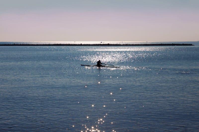 Mężczyzna na kajaku w błękitnym morzu przy wschodem słońca w Włochy obraz stock