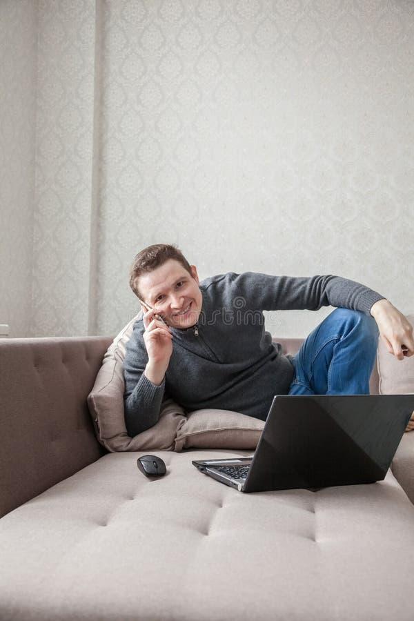 Mężczyzna na kanapie z laptopem obraz royalty free