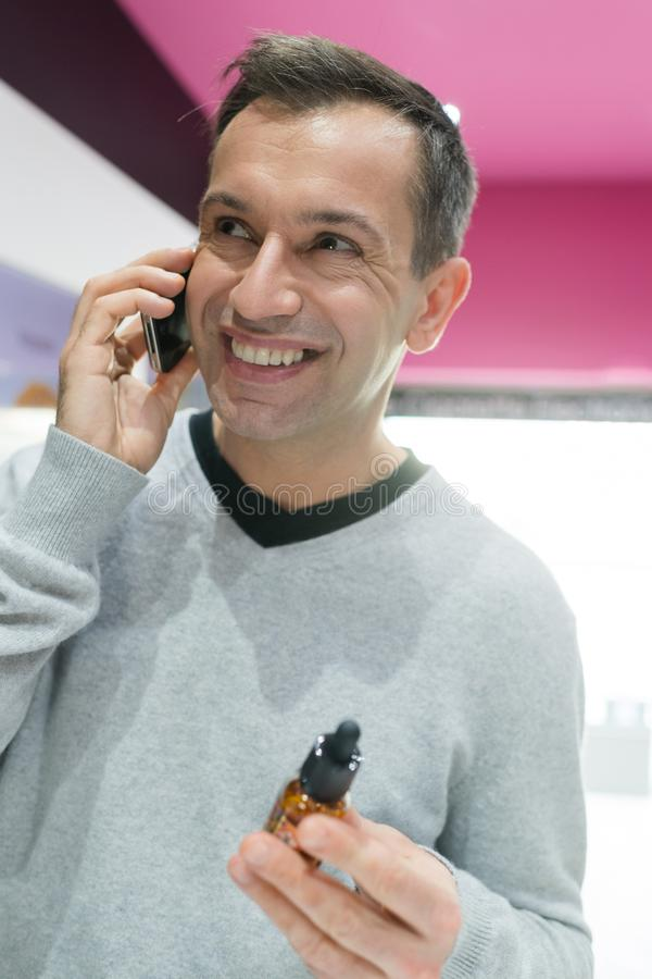 Mężczyzna na komórkowego telefonu mienia butelki vaporiser cieczu zdjęcia royalty free