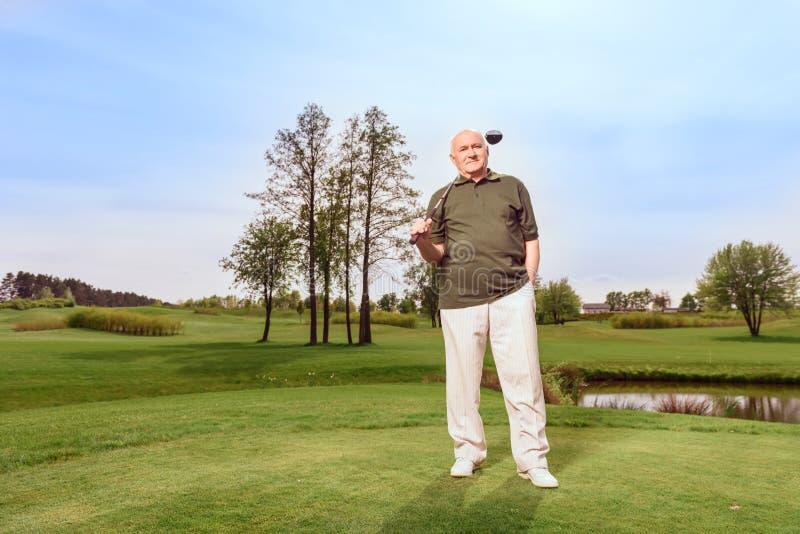 Mężczyzna na kursie z kijem golfowym przy ramieniem zdjęcie royalty free