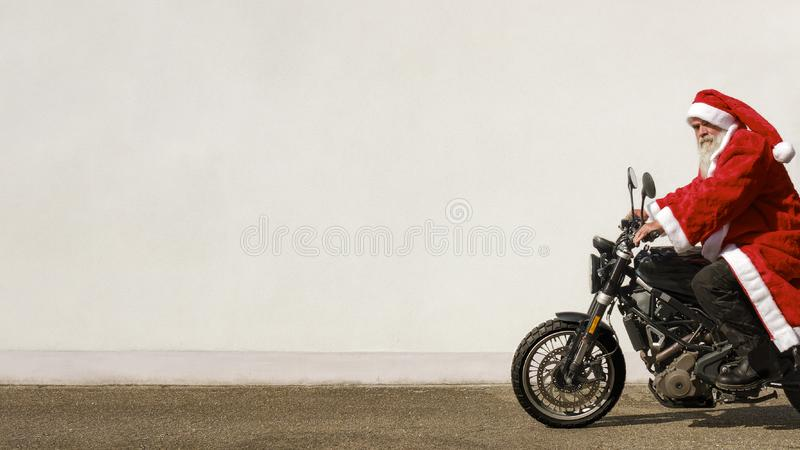 Mężczyzna na motocyklu w typowym Święty Mikołaj kostiumu obraz royalty free