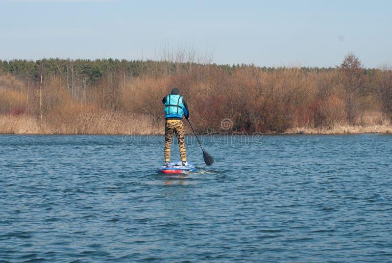 Mężczyzna na paddle desce na jeziorze w wczesnej wiośnie, nowożytne plenerowe aktywność na wodzie typ, obrazy stock