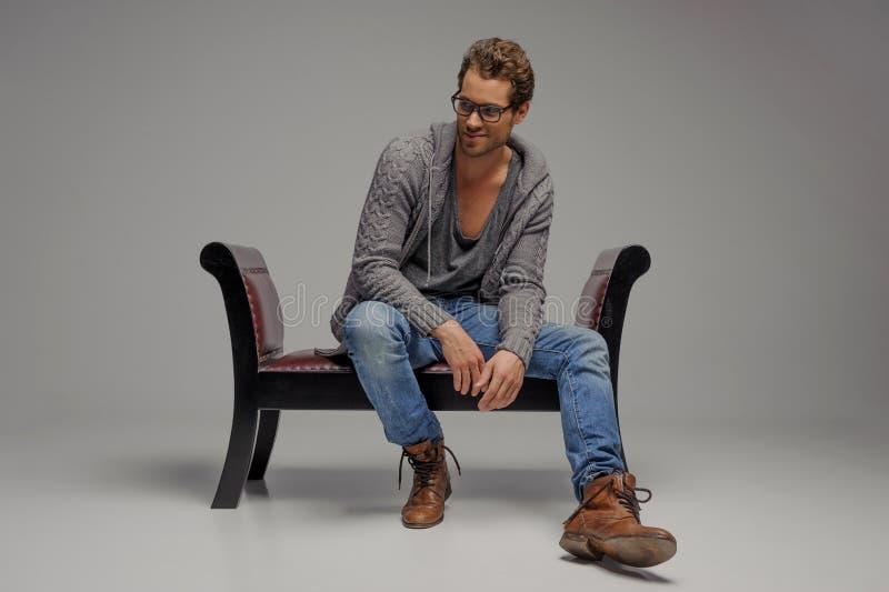 Mężczyzna na rocznika krześle. Przystojni młodzi człowiecy w szkieł siedzieć zdjęcie royalty free