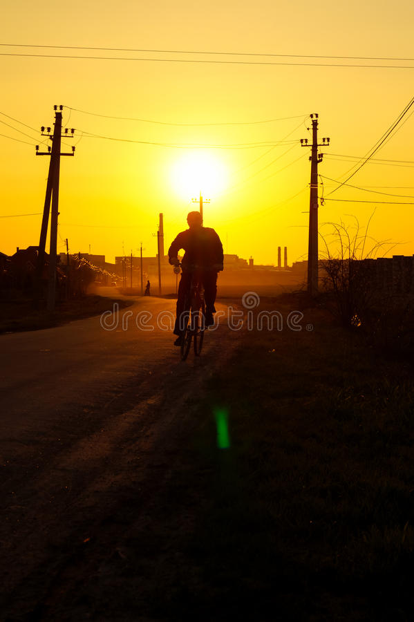 Mężczyzna na rowerze iść na drodze podczas zmierzchu fotografia stock